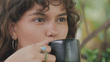 Face of a girl drinking coffee while she listens to someone