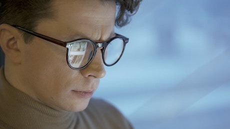 Face of a man with glasses using a tablet