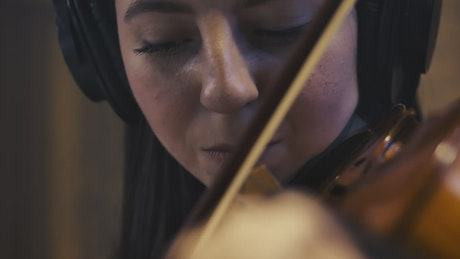 Face of a talented female violinist playing