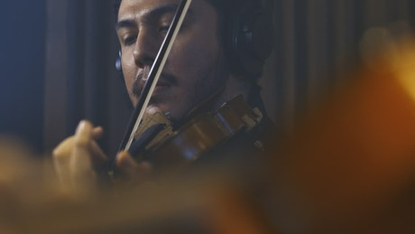 Face of a violinist playing in a recording studio