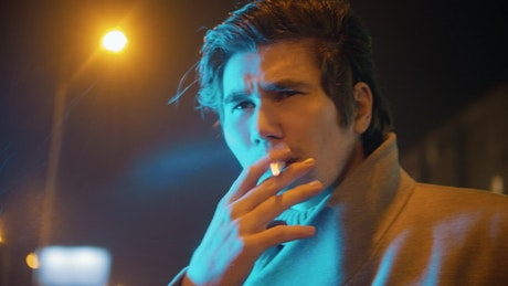 Face of a young man smoking on a rainy night