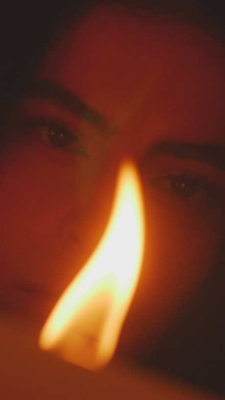 Face of a young woman appreciating the flame of a candle