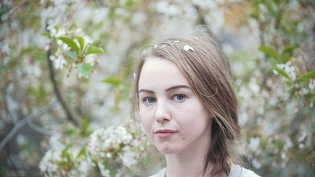Face of a young woman with a flowering tree behind