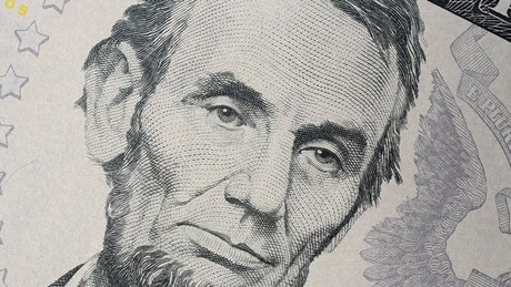 Face of Abraham Lincoln on a spinning banknote