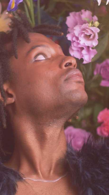 Face of an LGBTQ boy surrounded by flowers