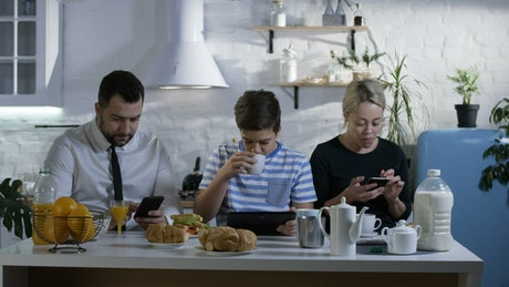 Family at breakfast watching their smartphones