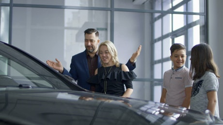 Family buying a new car in the dealership