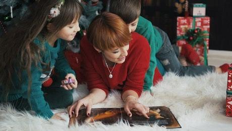 Family celebrates Christmas with cuddle near tree