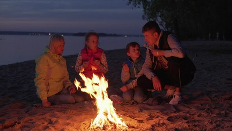 Family cooking over a campfire