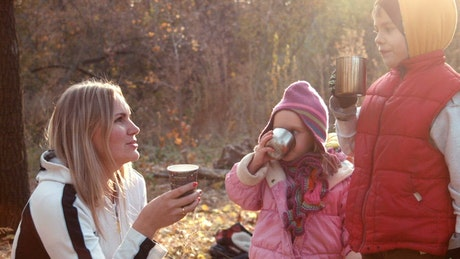 Family drinking a hot beverage in an autumn forest