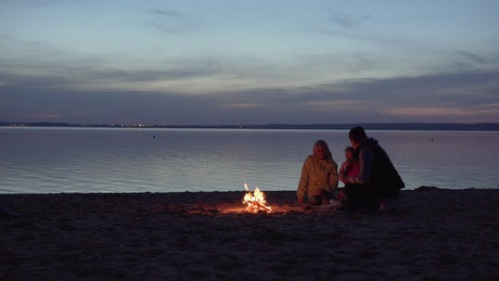 Family enjoying a campfire at the beach