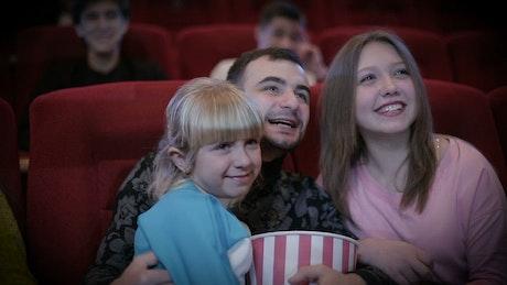 Family enjoying a movie at the cinema