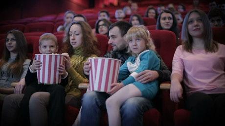 Family enjoying a movie at the cinema, medium shot