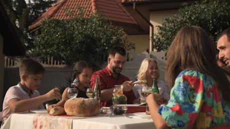 Family having dinner in the garden on a sunny day
