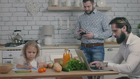 Family in the kitchen using gadgets