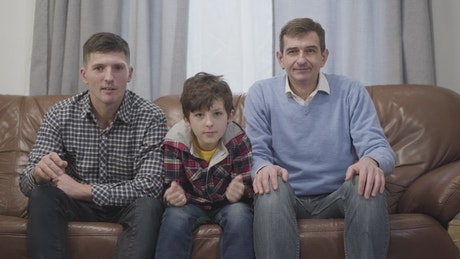 Family of football fans cheer on sofa watching game