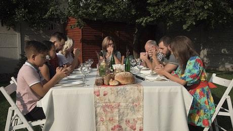 Family praying before dinner outdoors
