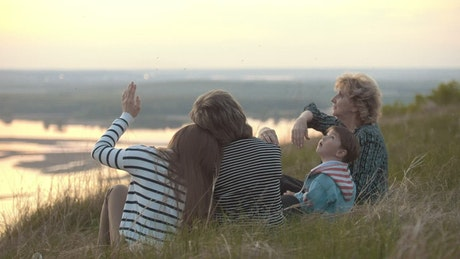 Family sitting on a hill watching the nature