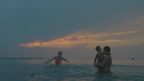 Family splashing out in the ocean