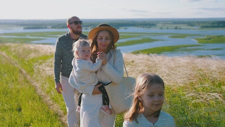 Family walking in a path in the meadow