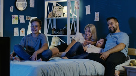 Family watching the TV in the bedroom
