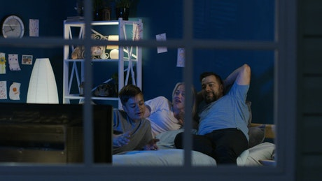 Family watching TV in the bedroom