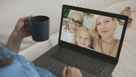 Family waves hello to woman on laptop video call