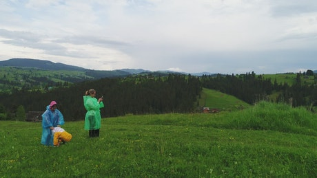 Family wearing raincoats taking selfies in nature