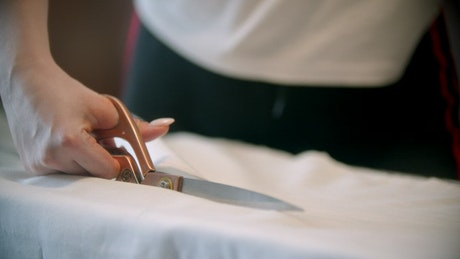 Fashion designer cutting fabric with a scissor