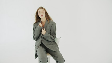 Fashion model sits posing with white background