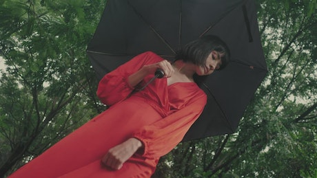 Fashion woman in red with an umbrella in a forest seen from below