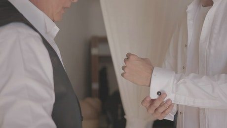 Father adjusting the cufflink to his son before his wedding