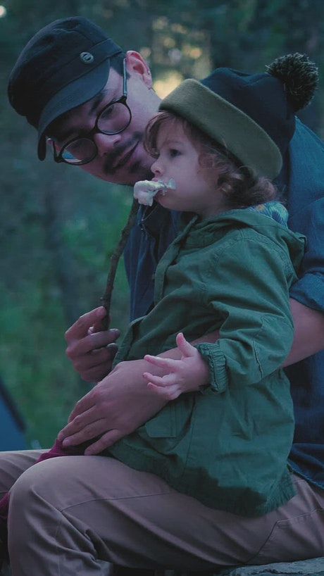 Father and his little daughter eating marshmallows in nature