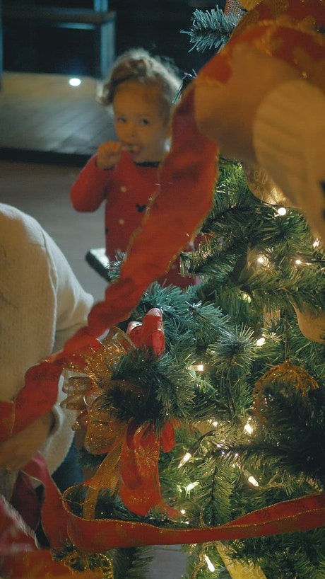 Father and mother decorating a Christmas tree