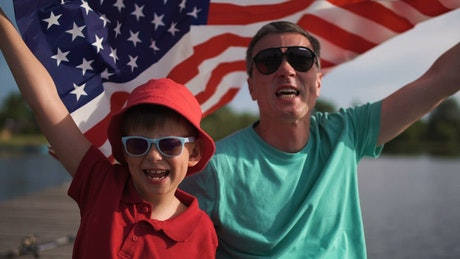 Father and son celebrating with an American flag