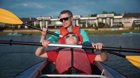 Father and son doing kayak in the lake