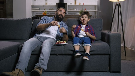 Father and son laughing at the TV
