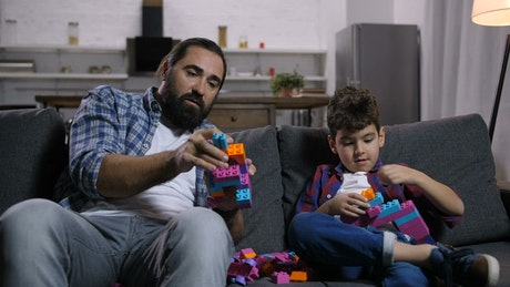 Father and son on a sofa playing with legos