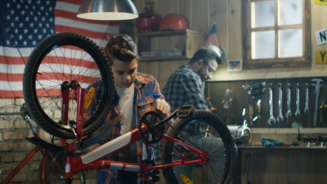 Father and son repairing a bike in the garage