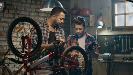 Father and son repairing a bike with tutorial