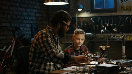 Father and son repairing a drone