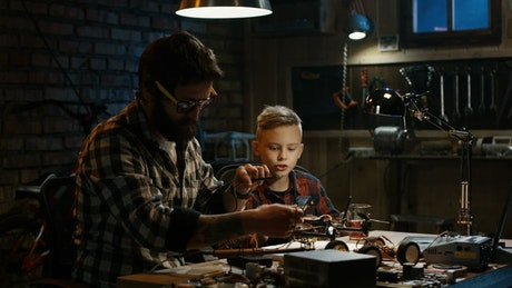 Father and son repairing a drone in the garage