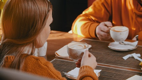 Father drinking coffee with his daughters