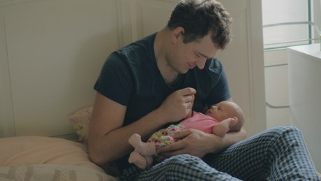 Father holding a newborns hand