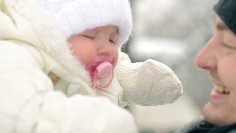Father looking and kissing his baby in winter