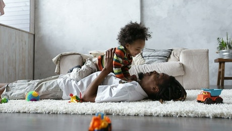Father playing on the carpet with his little son