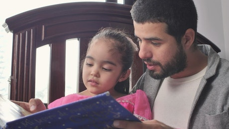 Father reading a story to his daughter in his arms