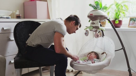 Father watching his newborn child sleep
