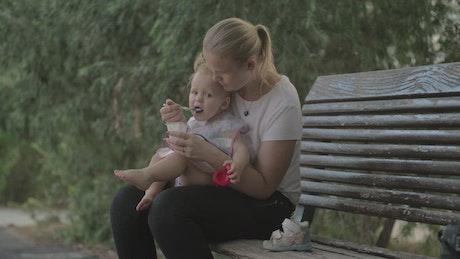 Feeding her young child a yogurt