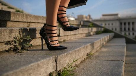 Feet in high heels of a woman walking down steps